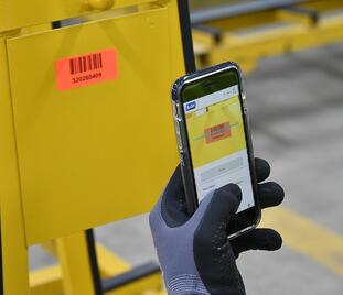 A smartphone and the A+W Smart Companion software are used to scan a barcode from a pane of glass.