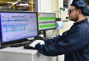 Ein Mitarbeiter arbeitet im Reinraum mit den A+W Production Terminals, die vor ihm auf den Monitoren angezeigt werden.