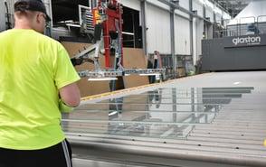Ein Mitarbeiter steht vor dem neuen Glaston FC-Ofen und spannt Gläser.