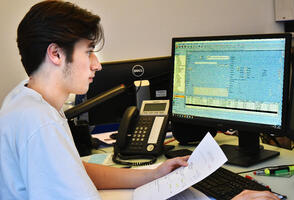 Ein Mitarbeiter sitzt im Büro an seinem PC und erfasst den Auftrag mit A+W Business.