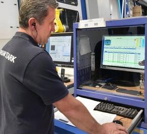 Ein Mitarbeiter steht vor einem Monitor und ihm wird das A+W Production Terminal darauf angezeigt.
