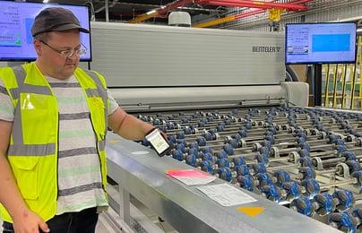 Ein Mitarbeiter steht an einer Arbeitsstation und scannt die Scheiben.