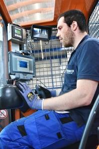 EinGabelstaplerfahrer sieht vor sich einen Monitor, worauf er sieht, welches Gestell wann auf welchen LKW geladen werden muss.