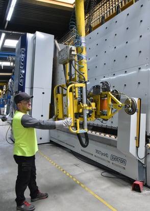 Ein Mitarbeiter steht vor der vertikalen Systron-Schleifmaschine und bearbeitet Rechteckscheiben.